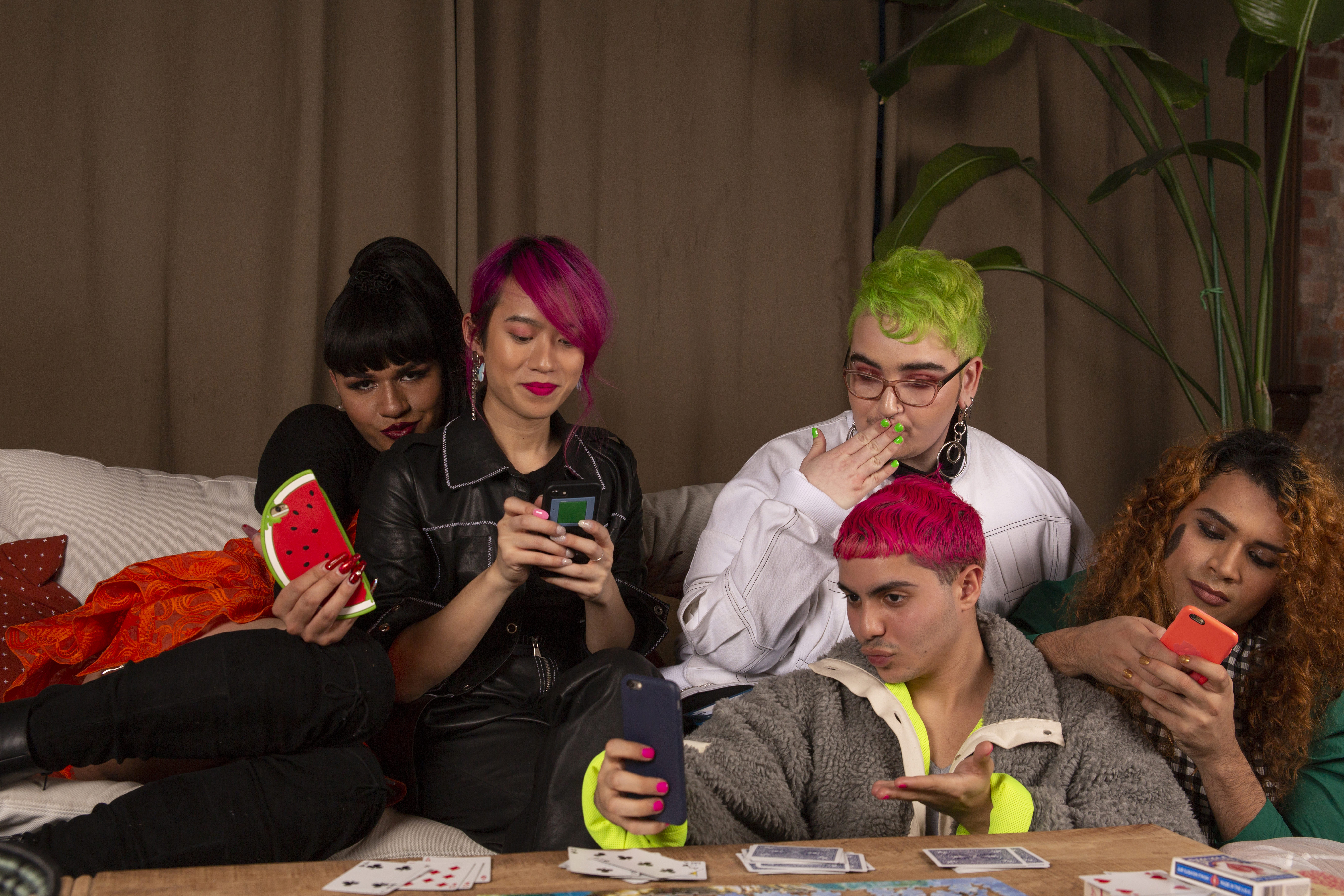 A group of friends of varying genders and sexualities taking selfies and surfing the net