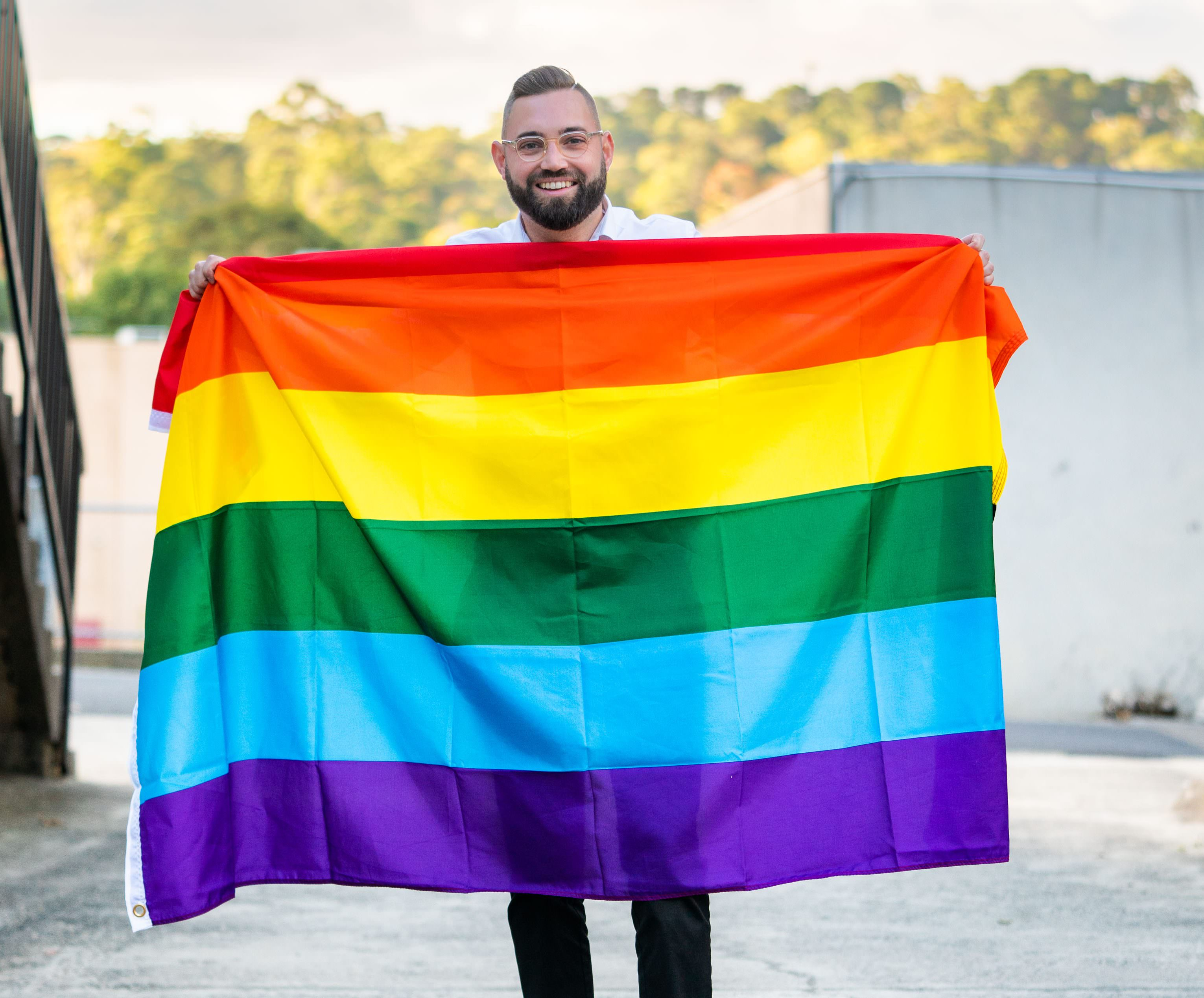A photograph of Dustin Halse, the Member for Ringwood. He is proudly holding a Rainbow flag.