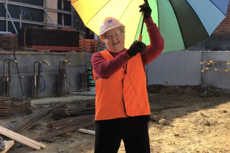 Jude on site holding Rainbow coloured umbrella