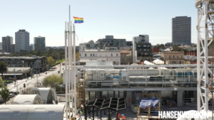 Drone footage of pride centre roof with flagpole flying the rainbow pride flag