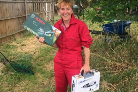 Ruth wears a red boiler suit whilst holding power tools in each hand, standing in the garden