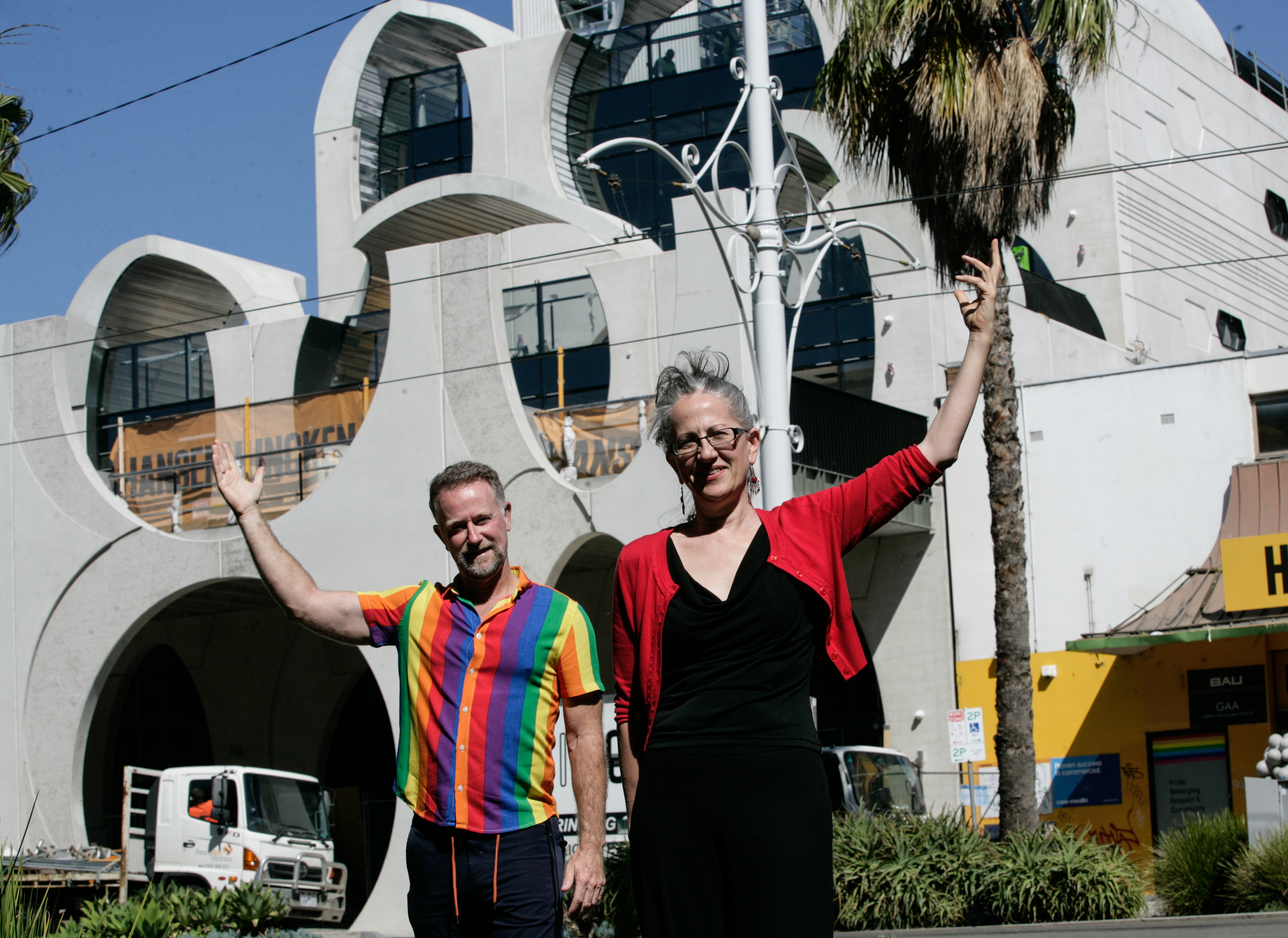 Stuart Kollmorgen from VPC and Karyn Bosomworth from Lord Mayors Charitable foundation stand in front of the pride centre on a sunny day pointing upwards. Stuart is wearing a rainbow shirt and Karyn is wearing black with a red cardigan. Photo Credit: Serge Thomann