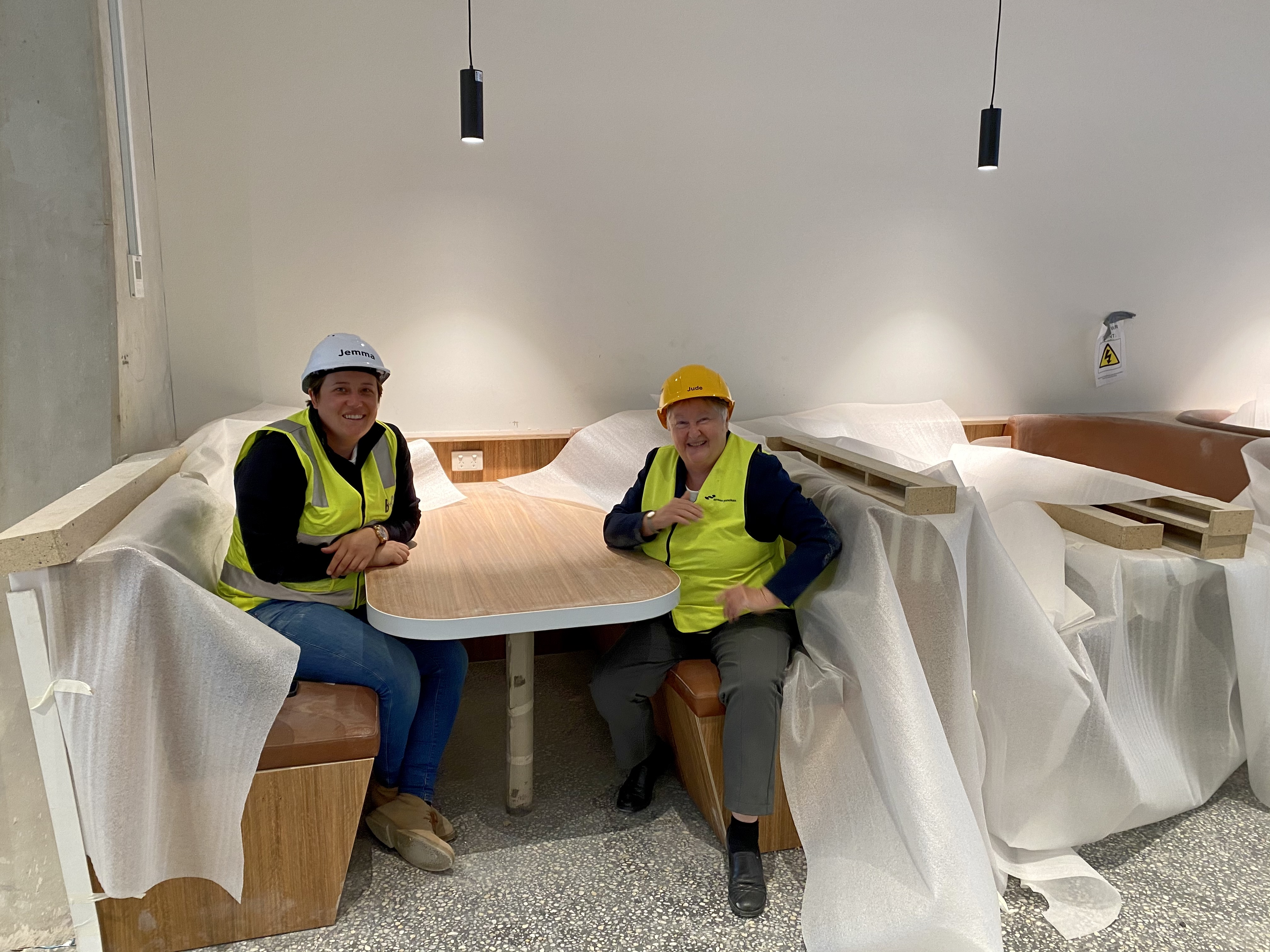 Photo of Jude Munro and Jemma Bates on the building site, sitting at a booth.