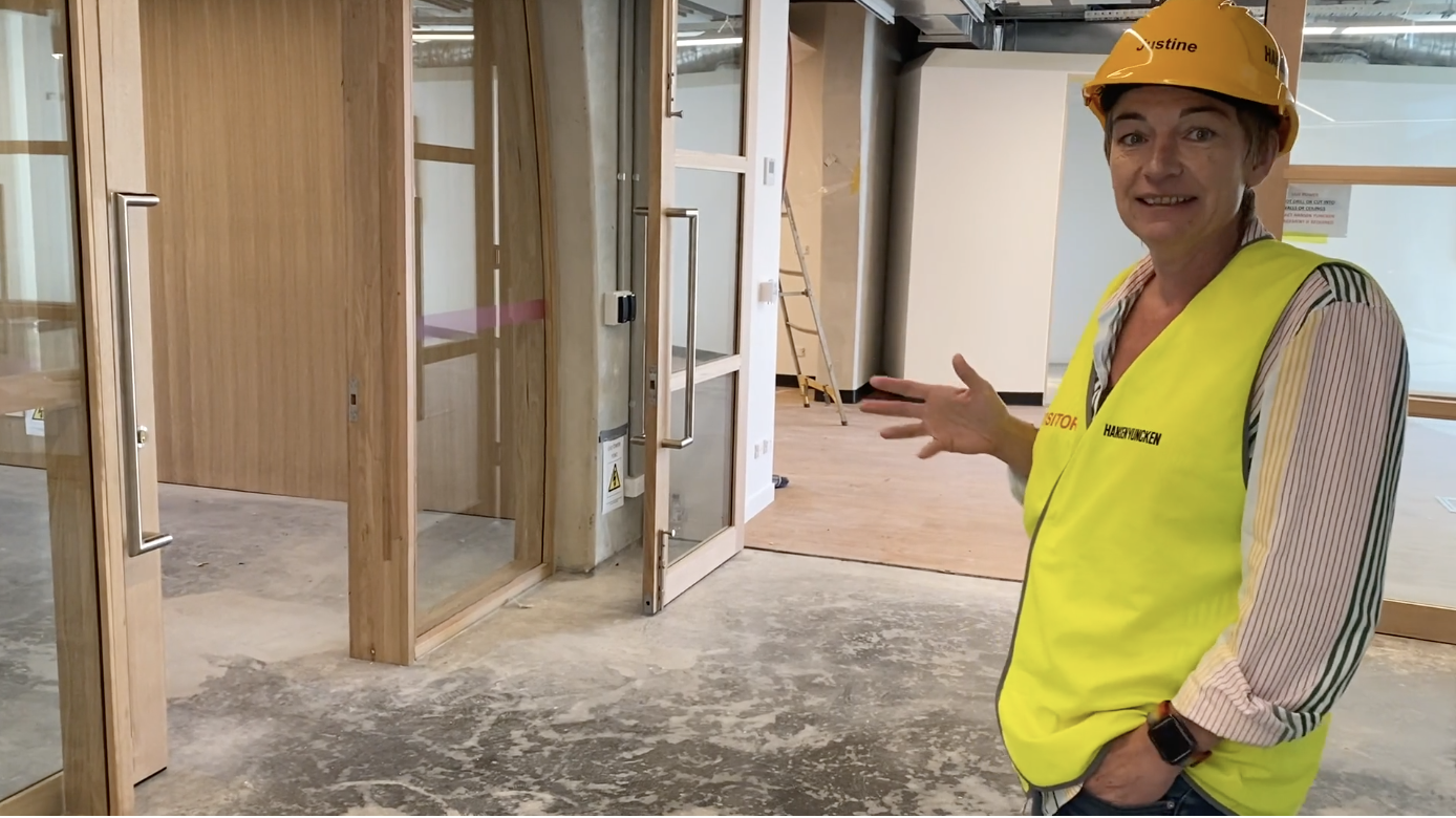 Photo of Pride Centre CEO standing on the first floor of the centre in yellow hi vis and safety helmet
